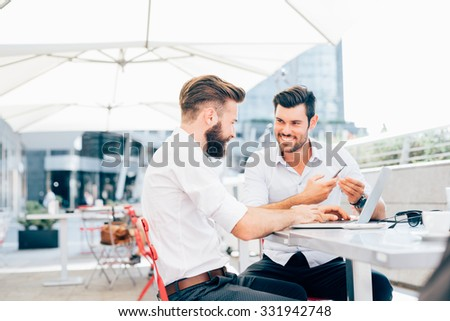 Two young bearded caucasian modern business man sitting in a bar, using smartphone and laptop, looking each other, smiling - business, work, technology concept  - stock photo