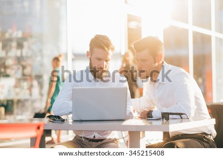 Two young bearded caucasian modern business man sitting in a bar, using smartphone and laptop, looking downward the screen, smiling - business, work, technology concept