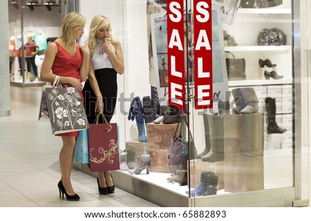 two young beautiful and elegant woman inside a commercial looking at a window shop - stock photo