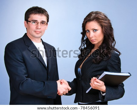 Two young beautiful business person shaking hands - stock photo