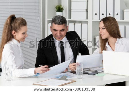 Two young beautiful business women consulting with their colleague. Partners discussing documents and ideas