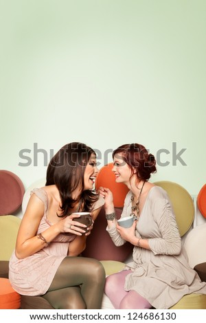 two young beautiful caucasian girls sitting on colorful sofa with coffee mugs in their hands, laughing - stock photo
