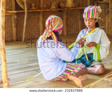 two young beautiful child girls in traditional clothes in bamboo house making toys from palm leaves, Philippines, Malay, Panay - stock photo