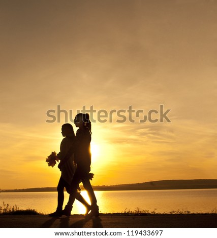 two young beautiful girl walking with a bouquet of maple leaves on sunset beach