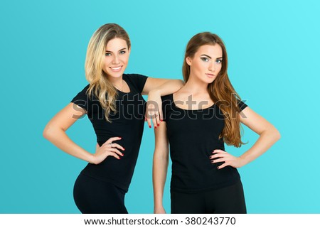 Two young beautiful girlfriends, athletic women in black clothes isolated at turquoise background