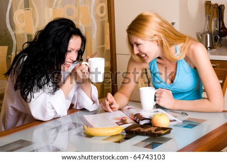two young beautiful girls drinking tea and talking in the kitchen at home - stock photo