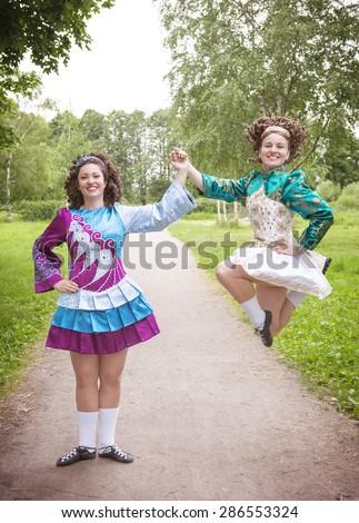 Two young beautiful girls in irish dance dress and wig dancing outdoor - stock photo