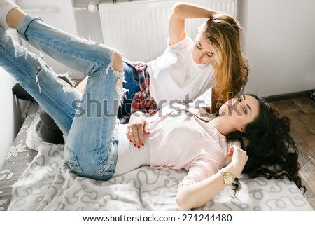 Two young beautiful girls laughing and posing in the bedroom sitting on the bed. Fresh style, lifestyle. - stock photo