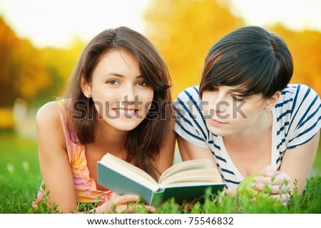Two young beautiful girls lying on the lawn and read a book