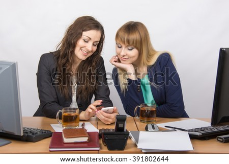 Two young beautiful girls office to discuss personal issues over a cup of tea - stock photo