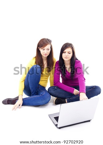 Two young, beautiful girls pointing at the laptop