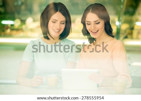 Two young beautiful girls sitting in urban cafe and using digital tablet. - stock photo