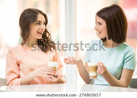 Two young beautiful girls sitting in urban cafe with coffee and talking.