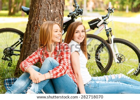 Two young beautiful girls with long hair sitting back to back on a blue checkered mat under a tree smiling happily, their bikes standing near in a green park, low angle - stock photo