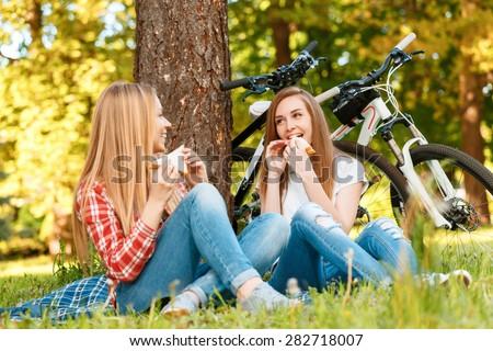Two young beautiful girls with long hair sitting on a blue checkered mat under a tree eating sandwiches and smiling, while their bikes standing near in a green park