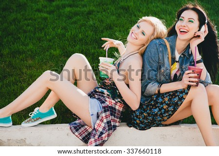 two young beautiful happy stylish girls, cocktail, smoozy drink, denim, smiling, happy, fashion, cool accessories, amazed, vintage style, having fun, park, sitting, grass, sneakers, background  - stock photo