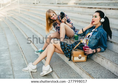 two young beautiful happy stylish hipster girls, cocktail drink, denim outfit, smiling, happy, cool accessories, vintage style, having fun, sitting, stairs, sneakers, headphones, camera, take photo