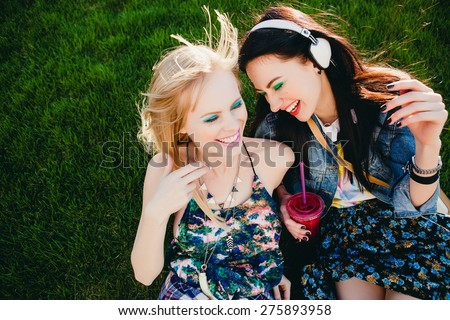 two young beautiful happy stylish hipster girls, friends together, cocktail, drink, denim outfit, smiling, fashion, cool accessories, vintage style, crazy having fun, park, sitting, grass, laughing - stock photo