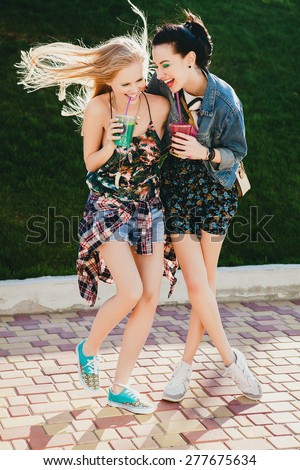 two young beautiful happy stylish hipster girls, friends together, cocktail, drink, denim outfit, smiling, happy, fashion, cool accessories, vintage style, having fun, park, crazy mood, laughing - stock photo