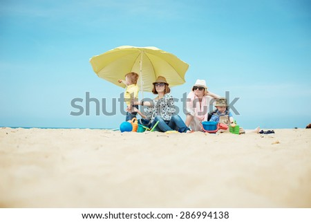 Two young beautiful mother with the boys on the beach