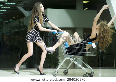 two young beautiful sexy playful girls with bright makeup and beautiful slender legs   - stock photo