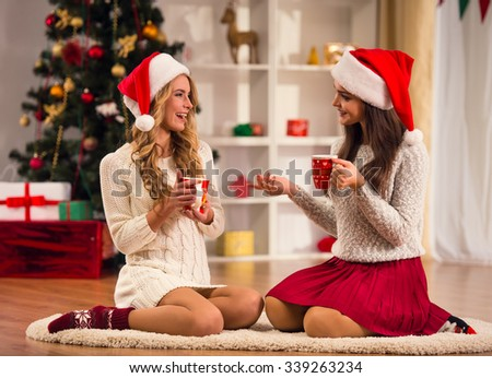 Two young beautiful woman drinks tea, celebrating Christmas at home - stock photo