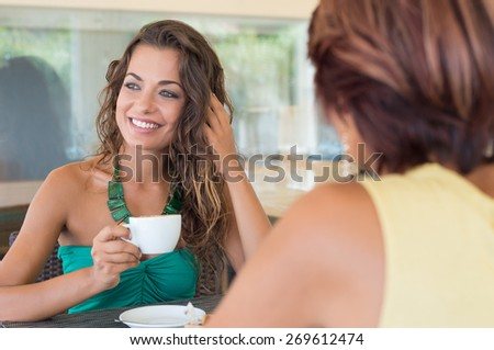Two Young Beautiful Woman Having Coffee At Bar