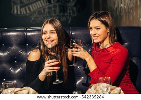 two young beautiful woman relaxing in the restaurant and drinking wine