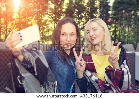 Two young beautiful woman relaxing on the terrace in the outdoor cafe. Two girls having fun making themselves self portrait photos on your mobile phone. Two women making selfie photo. - stock photo