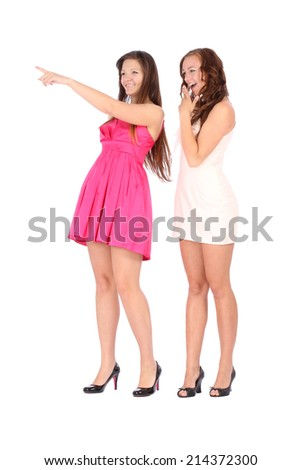 Two young beautiful woman smiling and pointing left over white background - stock photo