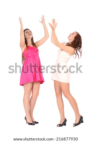 Two young beautiful woman smiling and pointing up over white background - stock photo