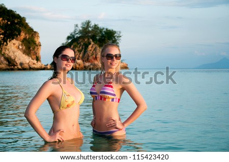 Two young beautiful women in bikini standing in water during sunset