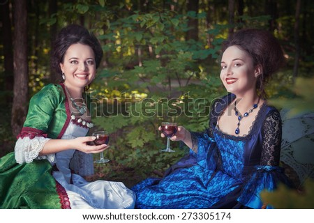 Two young beautiful women in long medieval dresses having picnic outdoor - stock photo