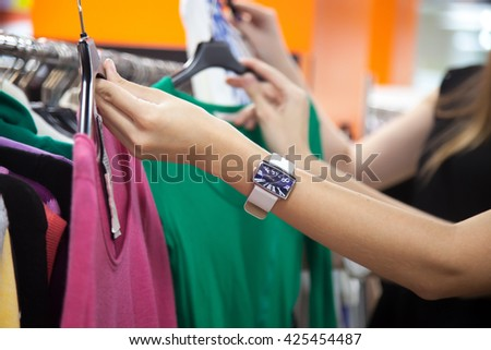Two young beautiful women shopping together, standing in the mall, choosing new clothes, holding hangers with different red and green casual blouses, deciding on color, close-up of hands