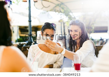 Two young beautiful women taking a selfie of themselves during lunch break
