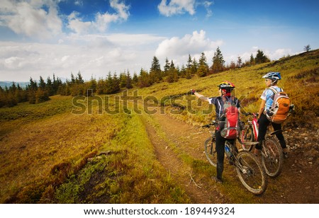 Two young bikers looking at the mountains - stock photo