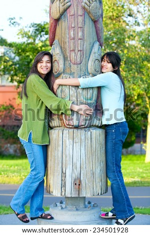 Two young, biracial teen girl in park hugging a totem pole on sunny day - stock photo