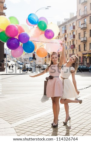 Two young blond women holding colorful latex balloons, urban scene, outdoors - stock photo