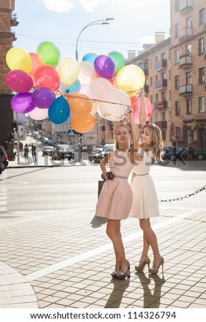 Two young blond women with colorful balloons, urban scene, outdoors - stock photo