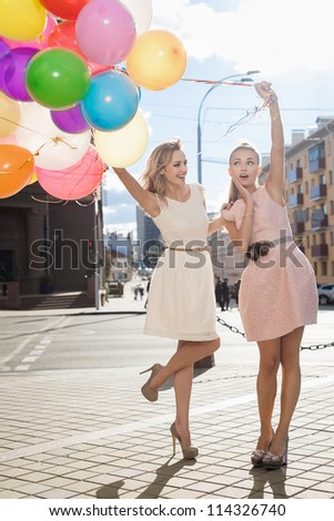 Two young blond women with colorful latex balloons, urban scene, outdoors - stock photo