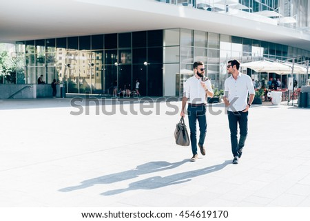 Two young blonde and black hair modern businessman, walking outdoor in the city, talking and chatting  - working, successful, business concept