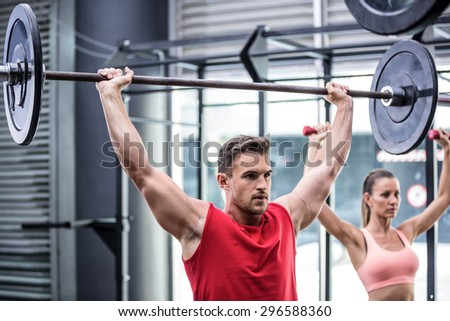 Two young Bodybuilders doing weightlifting in the crossfit gym - stock photo