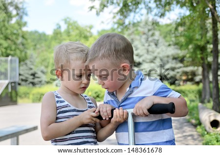 Two young boys arguing over a scooter both pulling on the handle bars as they decide whose turn it is to use it next - stock photo