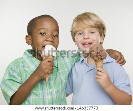 Two young boys eating ice cream cones - stock photo