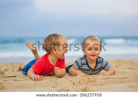 Two young boys having fun on a beach, happy best friends laughing