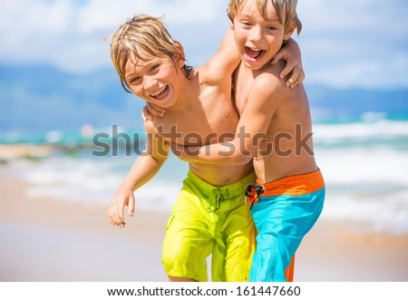Two young boys having fun on tropical beach, happy best friends playing - stock photo