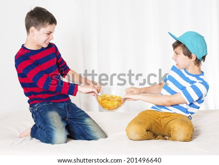 two young boys in bed and fighting over a bowl of potato chips - stock photo