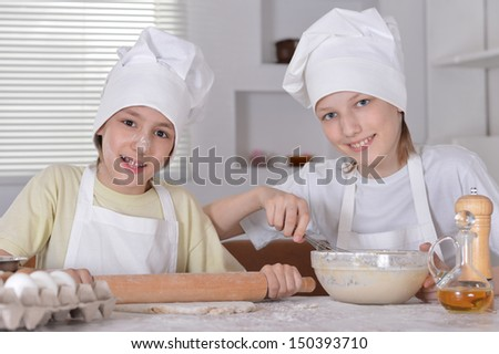 Two young boys knead the dough with a rolling pin for cookie