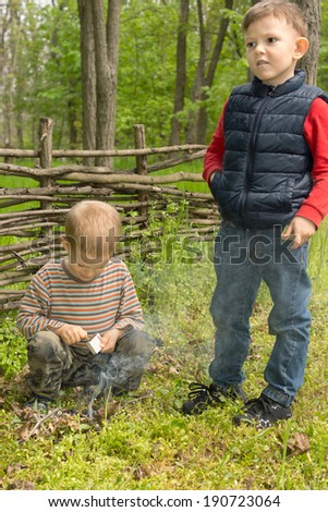 Two young boys learning survival skills trying to light a small campfire with a match as the one stands staring thoughtfully off to the side