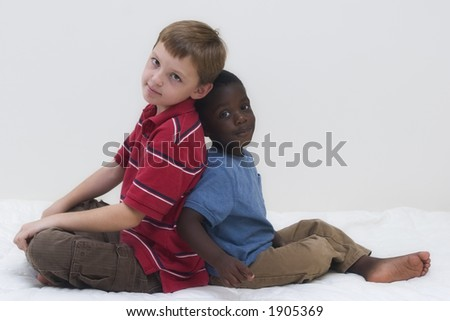 Two young boys of different races playing together.